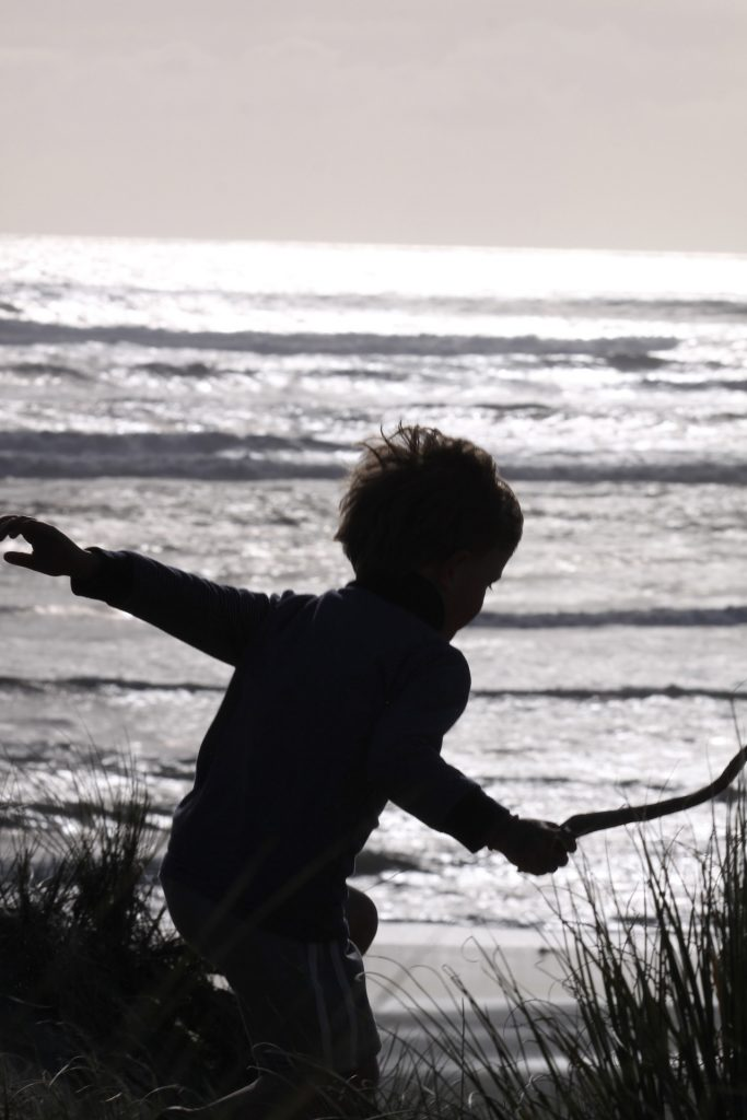 boy silhouetted on the beach with stick and sea