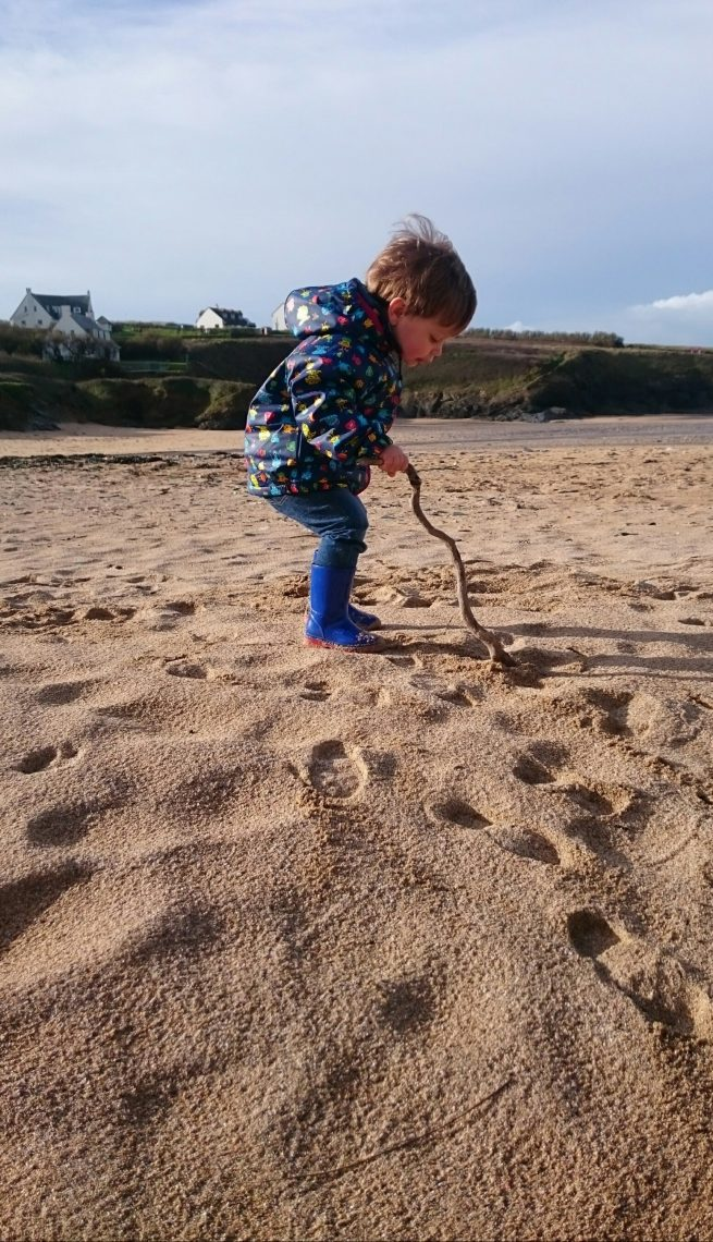 Little boy writing in the sand in Cornwall